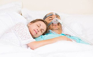 Woman and man with CPAP mask sleeping soundly