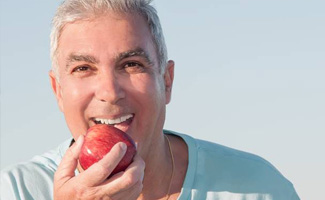 Smiling senior man eating an apple