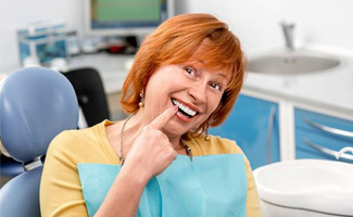 Smiling senior woman in dental chair pointing to teeth