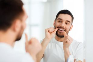 Smiling man flossing in the mirror