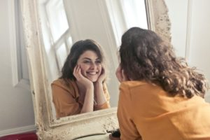 Woman looking in mirror after fixing small teeth