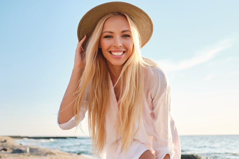 woman smiling outside at the beach during summer vacation
