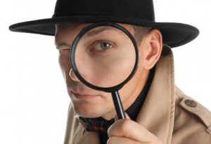 male detective looking through magnifying glass